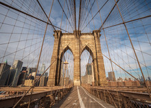 The Upper Deck Walkway Of The Brooklyn Bridge Facing The Manhattan Skyline During A Clear Sunny Day