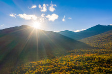 Aerial Shot With Sun Rays Flaring At Sunset From Behind Mount Washington, New Hampshire, On A Late Autumn Afternoon.