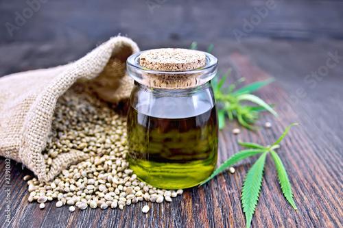 Oil hemp in jar with seed in sack on board