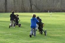 Junior Golfers Pushing Carts