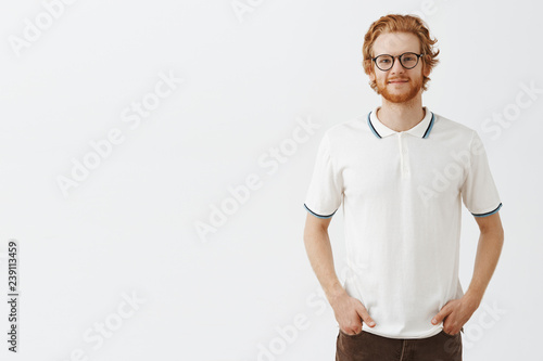 Foto  Studio shot of attractive ginger hair young male in prescribed glasses holding h