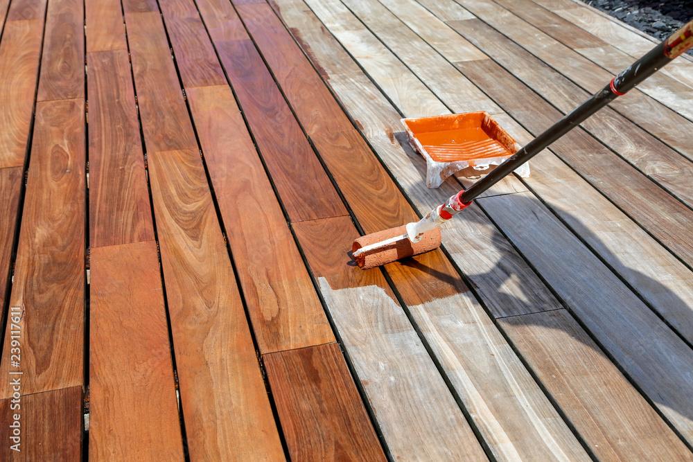 Fototapeta passage du saturateur sur terrasse en bois exotique