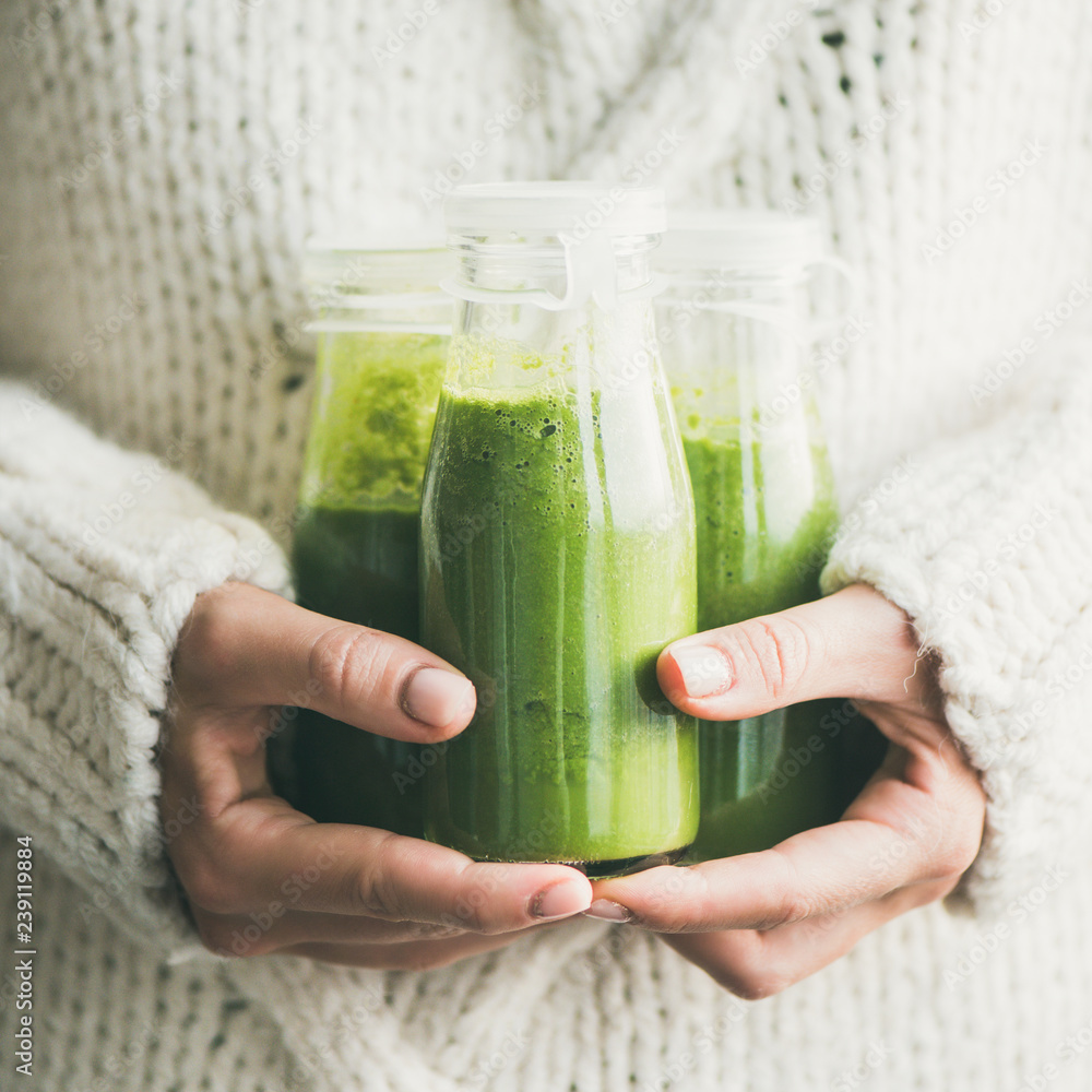 Fototapeta Winter seasonal smoothie drink detox. Female in light knitted sweater holding bottles of green smoothie or juice in her hands, square rop. Clean eating, weight loss, healthy dieting food concept