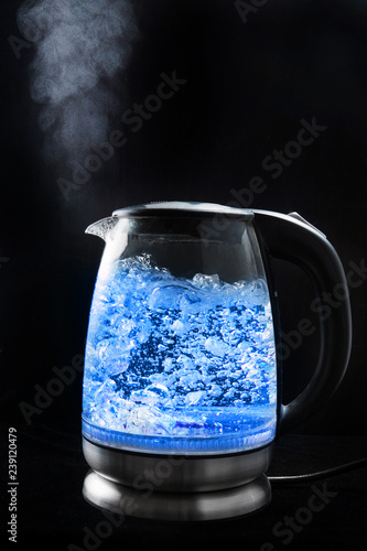 Fotografering  Boiling glass kettle with blue light on a black background, steam comes from the