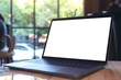 Mockup image of laptop with blank white desktop screen on table in cafe