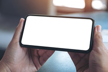 Mockup Image Of Hands Holding Black Mobile Phone With Blank Desktop Screen Horizontally