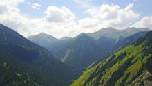 Green Hills And Mountains. The Hills Are Covered With Green Grass, Coniferous Forests. A Top View Shot With A Drone. Long Green Gorge.