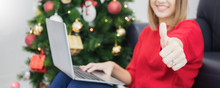 Asian Beautyful Woman Using Laptop Shopping Online And Show Thumb Up Hand With Decorating Christmas Tree In White Room At Home.Smiling Face And Happy To Celebrate New Year Festivel.