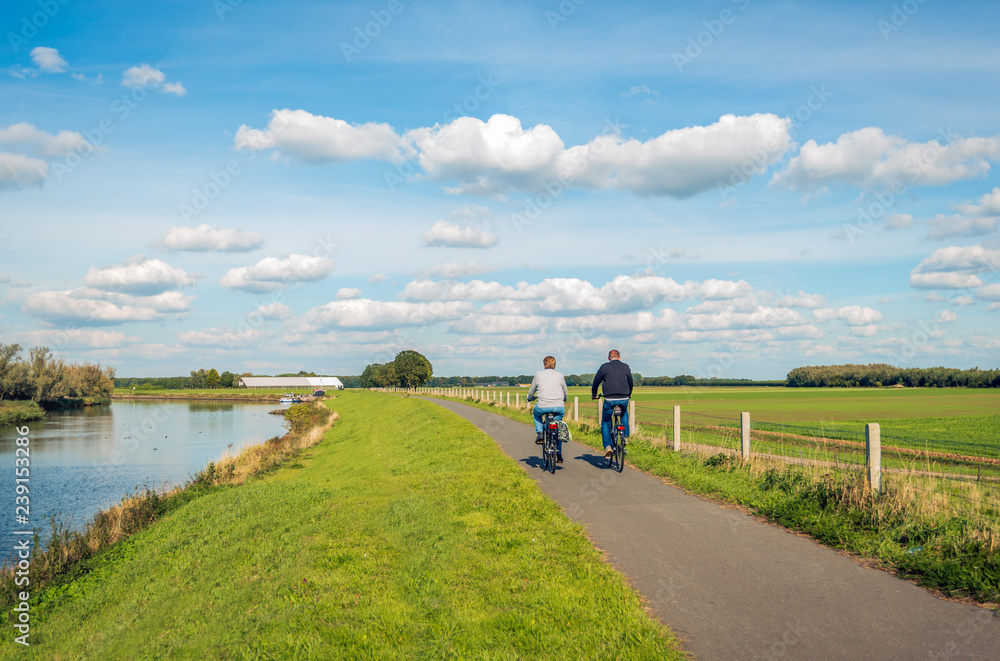 Fototapeta Two unidentified people cycle on a bike path at the top of a dike
