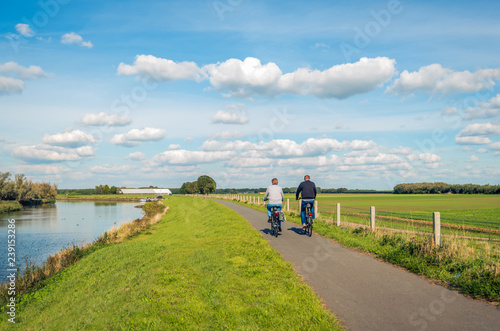 Foto Two unidentified people cycle on a bike path at the top of a dike