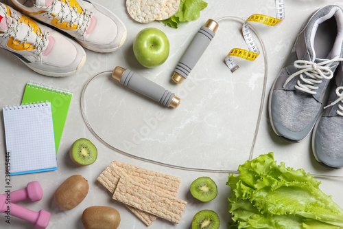 Flat lay composition with sport items, healthy food and space for text on grey background. Weight loss concept