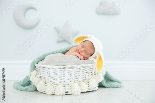 Adorable newborn child wearing bunny ears hat in baby nest indoors