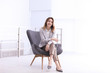 canvas print picture - Beautiful young businesswoman sitting in armchair indoors. Space for text