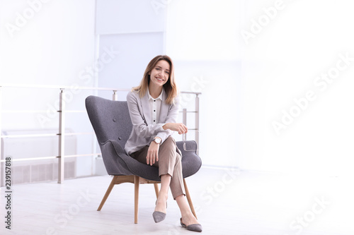 Beautiful young businesswoman sitting in armchair indoors Wallpaper Mural