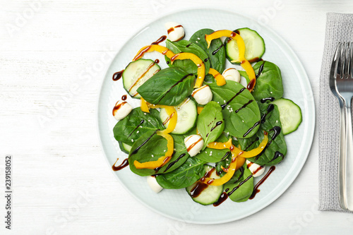 Fresh vegetable salad with balsamic vinegar served on wooden table, top view. Space for text