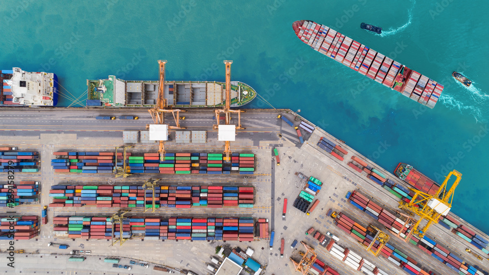 Fototapeta Aerial top view container ship at sea port and working crane bridge loading container for import export, shipping or transportation concept background.