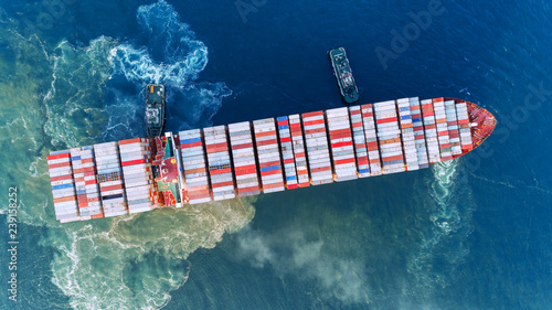 Fototapeta Aerial top view Tug boat drag container ship to sea port  for unloading container at crane bridge for import export, shipping or transportation