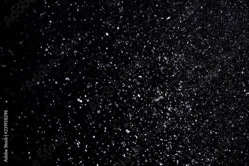 Fotografie, Obraz  Snow flakes falling on black background. Winter weather