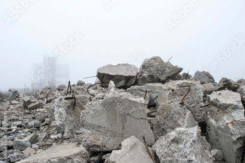 Fototapeta  The remains of concrete fragments of gray stones on the background of the destroyed building in a foggy haze