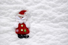 Christmas Soft Toy In The Form Of Santa Claus. The Toy Is Located Against The Background Of White Natural Snow. Santa Claus Is Dressed In A Red Fur Coat, A Cap And Black Valenoks