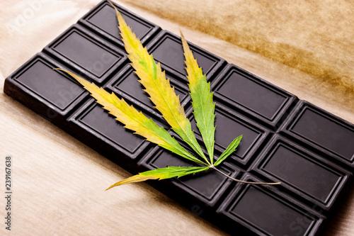Fotografie, Obraz  Marijuana leaf with an edible dark chocolate bar on the wrapping paper