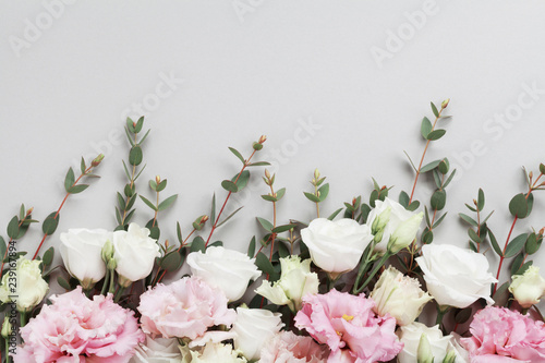 Beautiful floral border of pastel flowers and green eucalyptus leaves on gray table top view. Flat lay composition.
