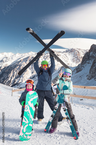 Kids and mom in ski school, mountains. Children learn skiing.