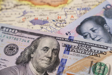 Chinese Yuan And US Dollars On The Map Of China. Trade War Between US And China, Economic Sanctions