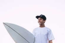 Nice Portrait Of Young Teenager With White Surf Board And T-shirt Smiling And Looking At His Side - White Clear Sky Background, For Male Surfer Athlete - Sea Life Lifestyle People