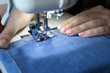 Female hands working on the sewing machine. Seamstress sews jeans, concept of wearing manufacture, textile industry, mending clothes