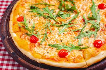 Pizza Margherita (Margarita) with fresh arugula on wooden board. Close up