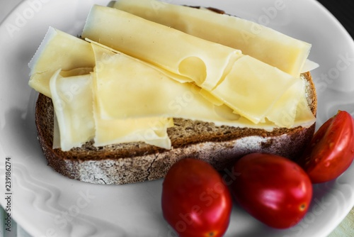 Sliced cheese on bread and cherry tomato.