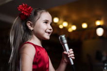 The Girl With The Microphone. A Small Child Sings Karaoke Closeup