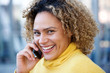 Close up happy african american woman with curly hair talking on mobile phone