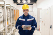 Portrait of young Caucasian man dressed in work wear using tablet while standing in heating plant.