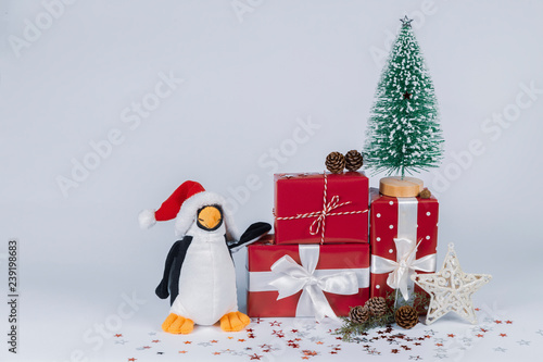 Fotografie, Tablou  Yoda with Santa Claus Hat stands near a little Christmas tree on gift packs with