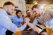 Group of mail friends drinking beer in a pub and having fun. Two man arm wrestling while other are supporting.
