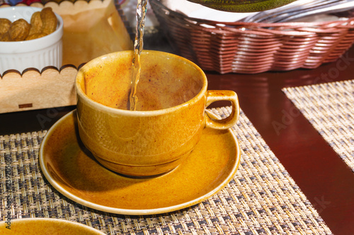 Fotografie, Obraz  green tea is poured in a thin stream into a yellow cup standing on a table among the food