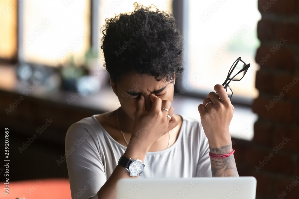 Fototapeta African American woman taking off glasses, feel eye strain, massaging nose bridge, tired female feeling discomfort after long wearing glasses at workplace, work with computer, bad eye vision close up