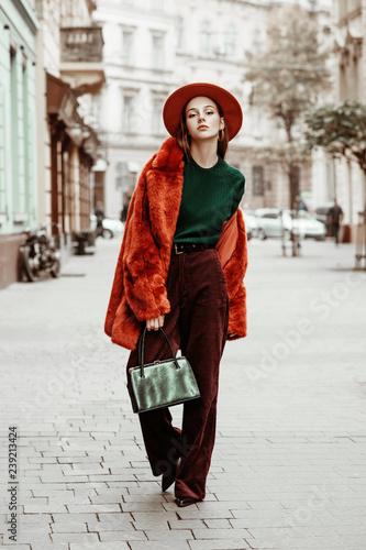 Outdoor full body fashion portrait of young beautiful woman wearing trendy oversized orange faux fur coat, hat, green sweater, corduroy trousers, holding stylish snakeskin bag, posing in street  Wall mural