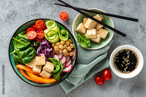 Buddha bowl salad with chickpeas, sweet pepper, tomato, cucumber, red cabbage kale, fresh radish, spinach leaves and tofu cheese, healthy balanced clean eating concept, top view, flat lay.