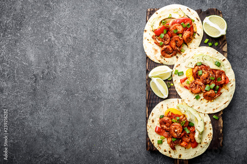 Fajitas in tortillas with fried shrimps, bell peppers and onion served up with avocado and green onions on wooden cutting board, top view, food background with space for a text