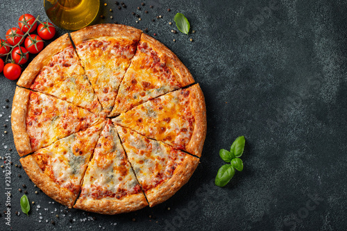 Delicious Italian pizza four cheeses with Basil, tomatoes and olive oil on a dark concrete table Poster Mural XXL