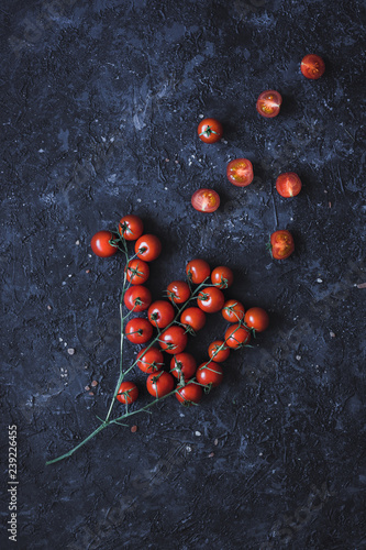 Printed kitchen splashbacks Branch of ripe cherry tomatoes on black background, top view.
