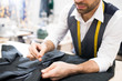 Mid section portrait of mature male tailor sewing classic jacket in traditional atelier studio, copy space