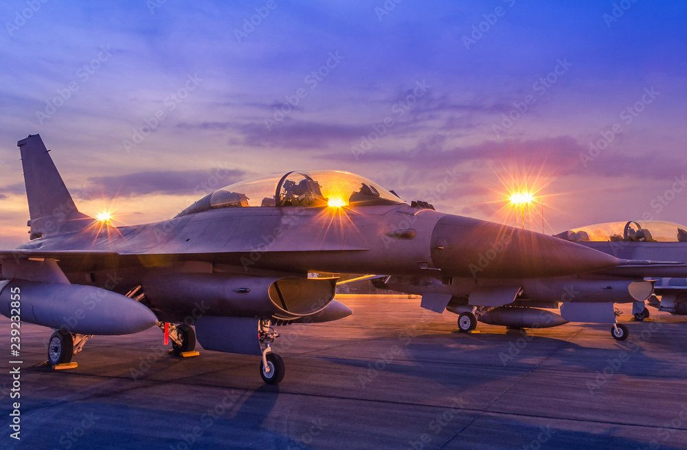 Fototapeta Silhouette fighter jet military aircrafts parked on runway in twilight time with light airport during air flight show in the night