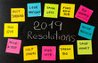 2019 Goals or New Year resolutions chalk handwriting and colorful post its memo notes on blackboard