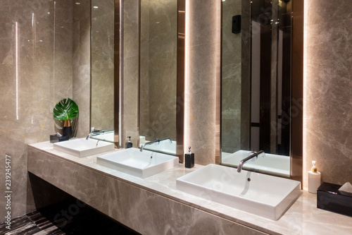 Row of modern marble ceramic wash basin in public toilet, restroom ...