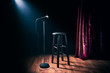 canvas print picture - microphone and wooden stool on a stand up comedy stage with reflectors ray, high contrast image