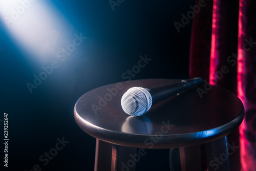 Obraz na plátně  microphone on a wooden stool on a stand up comedy stage with reflectors ray, hig